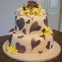 Purple Heart Cut-Outs With Calla Topper  My first cake in a while -- 2 tiered fondant with heart cutouts (using cutters purchased from Jennifer Dontz) -- topped with a sugar boquet...
