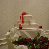 Four Tier Stacked Wedding Cake White Fondant The four tier stacked wedding cake was covered in ivory fondant with different designs on each tier, such as dots, quilting, etc. The bow...