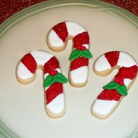 Candy Canes Rich Rolled Sugar Cookies with royal icing; both recipes from the Joy of Cooking. Decorated with red sanding sugar and hand-molded fondant...