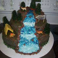 Waterfall Thanks to all the neat ideas on here, this is my concoction of a waterfall cake. Marble cake with BC icing, graham cracker tent, cone trees...