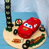 "Lightning Maqueen Cake  ""That cheeky car"" made for my sons fourth birthday. The cake was chocolate mud, filled with chocolate ganache and the tyres,..."