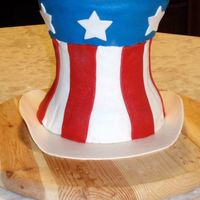 Uncle Sam's Hat Three layers of cakes. Chocolate and confetti cakes. Filling is a light and fluffy cheesecake. Iced in buttercream and covered with fondant...