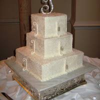 Bling!  3 tier, buttercream frosted cake, covered in sugar crystals. Gumpaste swirls andcandy diamonds painted with edible glitter, and hung from a...
