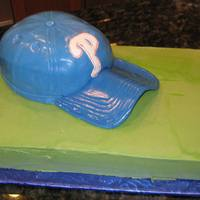 Phillies Baseball Hat Groom's Cake Phillies baseball hat on top of green field sheet for Groom