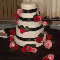 Black And Pink Wedding Cake  My first wedding cake! I worked off a picture the bride gave me.Alternating white and chocolate cake. BC frosting. Ribbon and roses are...