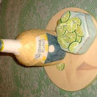 Corona With Lime   Bottle is bc with fondant bottle neck and lable. The limes are all made of fondant, sitting on a small cake covered with mmf.