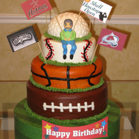 Sports Fan-Atic  4-tier multi-flavored cake frosted with all buttercream icing and fondant character. Wrapped styrofoam base. Bottom tier 12-inch, two-layer...