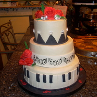 Musical Cake a 3 tiered cake with piano keys, and gumpaste red roses, stenciled fondant band.