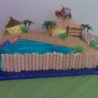 Luau Birthday Cake White cake, bavarian cream filling, whipped cream frosting, graham cracker sand, gel water. Little mini cake cabanas.