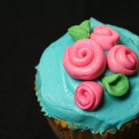 Rosebud Cupcake butter yellow cupcake w/ buttercream frosting in Teal. Satin Ice ribbon roses on top.
