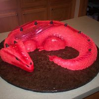 Red Dragon White cake iced in buttercream dream, covered in individual hand cut fondant scales, airbrushed with cranberry luster dust. Board dragon is...