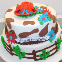 Western Cake Western style birthday cake. fondant flowers/cowboy hat/cow spots, rest is buttercream