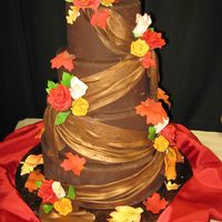 Fall Wedding Dummy cake made for the Bridal Fair covered in chocolate Satin Ice Fondant with drapes and gumpaste flowers. The drapes are painted with...