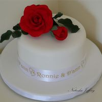 Red Roses Anniversary 6 inch fruit cake with gumpaste roses covered in FondX for an anniversary. I had the ribbon made with their names on it.Thanks for looking...
