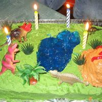 Top Of The Food Chain  Dinosaur themed cake complete with blue Jello 'lake' and erupting volcano. Used plastic dinos on the cake so each child could...
