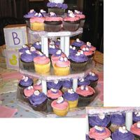 "Its A Girl Cupcake Tower  Chocolate and vanilla cupcakes on a cakeboard tower iced with buttercream icing and topped with sugar baby heads and booties. ""Its a..."