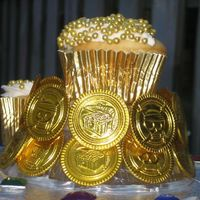 Pirate Booty Cupcake Tower Topper Close up of the topper for the Pirate Booty Cupcake Tower. Glue gunned plastic 'gold' coins to the stand and encrusted the...