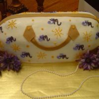 Designer Purse Cake This was my first attempt at a purse cake. It was a red velvet cake with BC icing and fondant handles and decals.