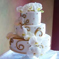 Gold Vines And Orchids Three tier wedding cake iced in buttercream. Handpainted gold fondant vines and dots. Real orchids.