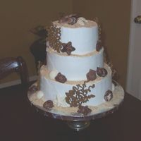 Beach Wedding Cake   The cake is chocolate with white buttercream icing, chocolate seashells and royal icing coral. The sand is ground Nilla wafers.
