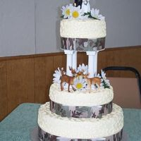 Camoflage Wedding Cake This wedding cake was made with camoflage ribbon on each tier. fake daisies and plastic deer.