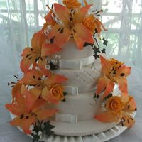 Picture_291.jpg Three tier round wedding cake with gumpaste apricot roses and peach oriental lilies covered in ivory fondant, all flower were handmade by...