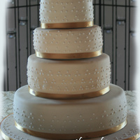 Off White Swiss Dots This is my first wedding cake. Bride wanted off white with white royal icing swiss dots and gold ribbon. 14, 10, 8, and 6 inch 4 layer...