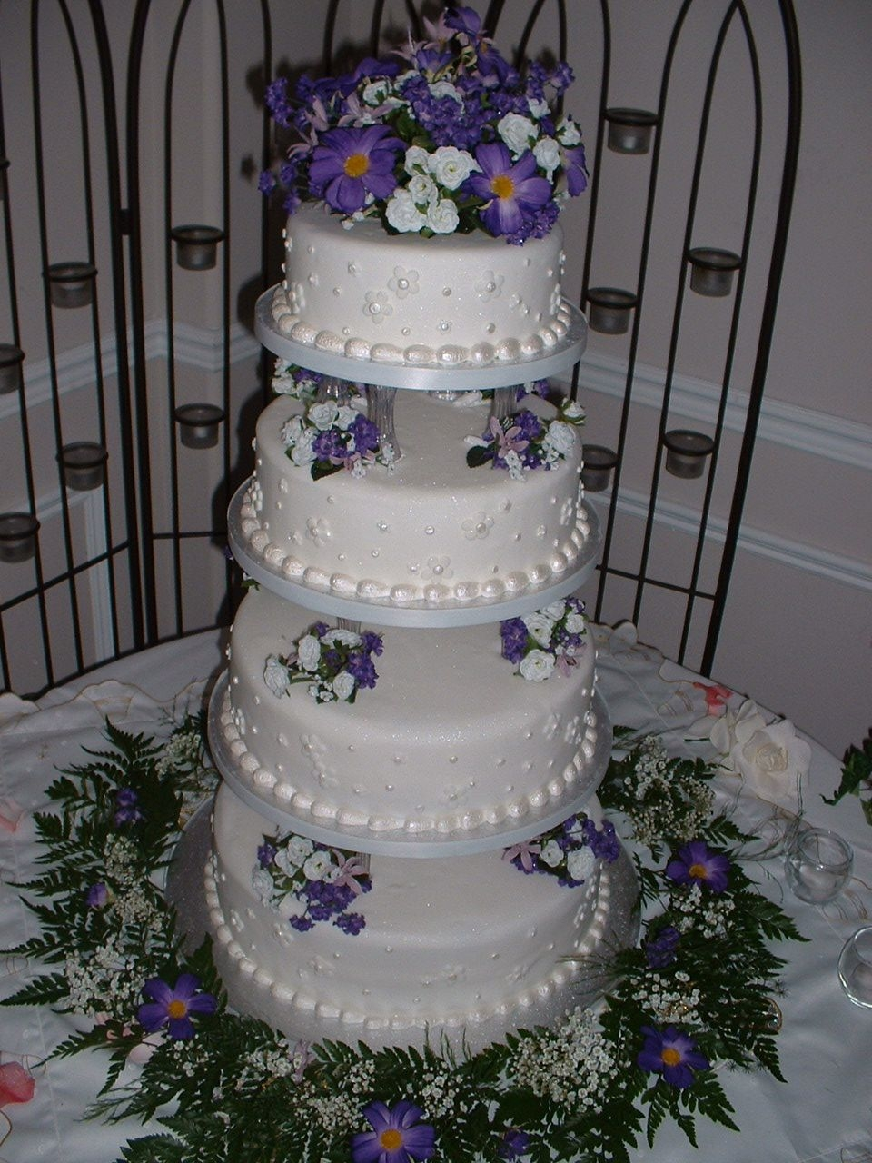 Purple Flowers Wedding Cake Four tiers made with push in pillars (top tier was artificial) and silk flowers. 14-12-10-8 inch tiers.