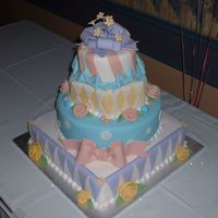 Dscf0031.jpg Everything on this cake is edible, except for the flower wires in the gumpaste bow. The design of this cake is based on a design by Sharon...