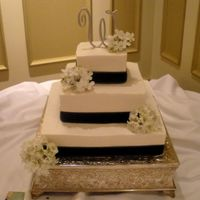 Black And White White bc with buttercream icing. Black ribbon and silk flowers. The bride provided those things. 14, 10, 6 inch cakes. It was my first set...