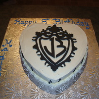 Jonas Brothers Cake   This is a cake I made for my 8 year old daughter who loves the Jonas Brothers. The crest is made from black fondant.