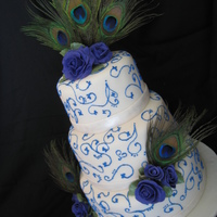 "Peacock Wedding Cake  Fondant covered. Handmade purple gumpaste roses. Blue RI scrolls and swirls. Pearl dusted fondant ""ribbon"". Peacock feathers are..."