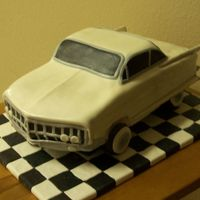 1962 Cadillac Cake was carved from a 1/2 sheet pan, 4 layers. I used blocks spray painted black to lift it up, wheels are doughnuts, covered in mmf.