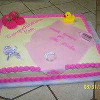 Thank Heaven For Little Girls yellow cake with pastel yellow buttercream icing and dark pink border. Blanket is light pink fondant. Booties are made of Marshmallows and...