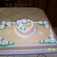 "With This Ring Bottom is yellow 1/2 cake with ivory buttercream icing. Heart is a 6"" yellow cake. White Roses and shell border. Doves and rings are..."