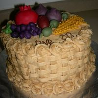 Bikurim Fruit Basket - Side View fruit basket including pomegranate, grapes, dates, figs, olives and wheat, celebrating the Jewish holiday of harvest. choc. chip cake with...