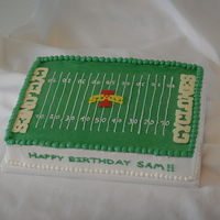 Football Field choc 1/4 sheet cake iced in buttercream. Logo done in choc transfer, candy melts for the endzone