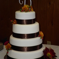 Round Fall Wedding Cake 12, 10, 8, 6 inch round cakes covered in MMF. Used fabric ribbon in chocolate brwn and real flowers as accents! Bride LOVED it! :)