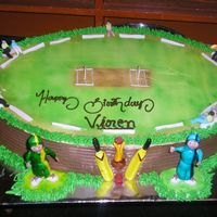 Cricket Theme Cake The cake is shaped as the field with sugarpaste characters and 2 players kept in fromt, along with the bat, ball and trophy. enjoy this...