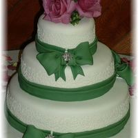 "Green Bows And Lace three tiered wedding cake 14"",10"" and 6"" cakes. All covered in white fondant. Buttercream cornelli laced piped around each..."