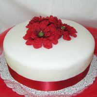 Red Velvet Fondant covered cake with fake silk flowers and ribbon