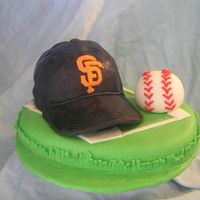 Halloween_2006_052.jpg Cake for son's baseball team. 6 inch round cake with half of ball cake on top. Hat bill is made of cardboard covered with fondant....