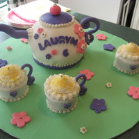 Tea Party Cake Cake covered in MMF. Tea cups are cupcakes.