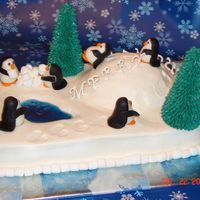 Playful Penquins Butter pecan cake covered with BC icing. Decorated with MMF penquins, ice cream cone trees and piping gel pond.