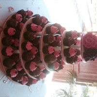 Cupcake Wedding Cake Fuschia and chocolate cupcake tower with gumpaste roses. Mudcake with whipped chocolate ganache and fuschia whipped white chocolate ganache...