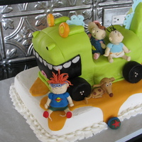 Rugrats The Movie  Kids made out of gumpaste, dinosaur is pound cake covered in fondant, bottom cake is white cake, strawberry filling with buttercream. What...