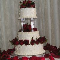 Scroll/rose Wedding Cake white buttercream frosting, scrolls on each tier, fresh red roses between tiers