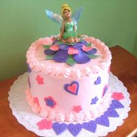 Tinkerbell Sitting In Flower Tink and flower are gumpaste. Hearts and flowers on cake are fondant.