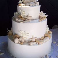 Three-Tier White Wedding Cake With Seashells, Coral And Pearls For a wedding by the ocean. Buttercream frosting, gum paste and chocolate seshells.