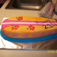 Surfboard birthday cake for a friend who likes surfboards and all of that fun stuff. it is fondant that has been painted. there are little flowers...